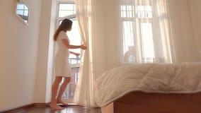 Νέο όμορφο κορίτσι στην άσπρη πόρτα μπαλκονιών φορεμάτων ανοίγοντας στην κρεβατοκάμαρά της φιλμ μικρού μήκους