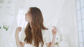 Νέο όμορφο κορίτσι στο άσπρο ντεκόρ κίνηση αργή απόθεμα βίντεο
