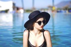 Νέο όμορφο κορίτσι στο μαύρο καπέλο μόδας, δέρμα βελούδου, κόκκινα χείλια, μαύρη τοποθέτηση μαγιό στη λίμνη στο μπλε νερό, μοντέρ στοκ φωτογραφία με δικαίωμα ελεύθερης χρήσης