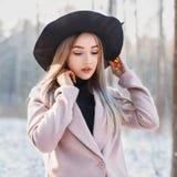 Νέο όμορφο κορίτσι στο μοντέρνο μαύρο καπέλο και παλτό σε ένα backgrou Στοκ Φωτογραφίες