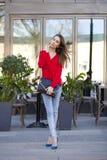 Νέο όμορφο κορίτσι στο τζιν παντελόνι και κόκκινο πουκάμισο στο backgrou Στοκ εικόνα με δικαίωμα ελεύθερης χρήσης