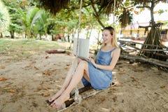Νέο όμορφο κορίτσι χρησιμοποιώντας το lap-top και οδηγώντας στην ταλάντευση στην άμμο στοκ φωτογραφία με δικαίωμα ελεύθερης χρήσης