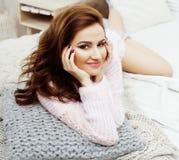 Νέο όμορφο κορίτσι brunette που βάζει στο άνετο κρεβάτι με τον καφέ που φορά το ευτυχές χαμόγελο χειμερινών πουλόβερ μαλλιού, άνθ Στοκ φωτογραφίες με δικαίωμα ελεύθερης χρήσης