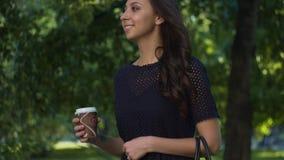 Νέο όμορφο κορίτσι brunette που περπατά στο θερινό πάρκο με τον καφέ για να πάει, χαμόγελο φιλμ μικρού μήκους