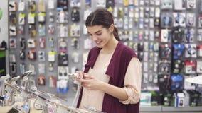 Νέο όμορφο κορίτσι brunette που χαμογελά τυλίγοντας ένα iPhone που δένεται στο ράφι επίδειξης στο κατάστημα συσκευών Επιλογή νέα φιλμ μικρού μήκους