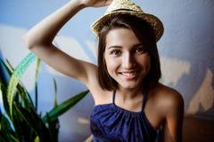 Νέο όμορφο κορίτσι brunette στη συνεδρίαση καπέλων στα σκαλοπάτια, χαμόγελο Στοκ Φωτογραφία