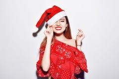 Νέο όμορφο κορίτσι brunette στο χαμόγελο καπέλων Χριστουγέννων Κόκκινα χείλια, κόκκινα καπέλα Στοκ Εικόνες