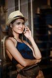 Νέο όμορφο κορίτσι brunette στο χαμόγελο καπέλων, που μιλά στο τηλέφωνο Στοκ εικόνες με δικαίωμα ελεύθερης χρήσης