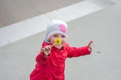 Νέο όμορφο μωρό κοριτσιών σε ένα κόκκινο σακάκι και λευκό παιχνίδι καπέλων στην παιδική χαρά στο πάρκο σαλαχιών, που εισπνέει το  Στοκ Εικόνα