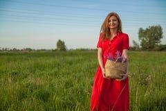 Νέο όμορφο ξανθό γυναικών με τα λουλούδια στη φύση το καλοκαίρι στοκ εικόνες