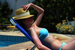 Νέο όμορφο ξανθό κορίτσι που κάνει ηλιοθεραπεία μια θερινή ημέρα σε έναν αργόσχολο από τη λίμνη Στοκ φωτογραφία με δικαίωμα ελεύθερης χρήσης