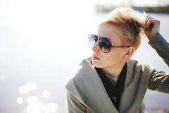 Νέο όμορφο ξανθό κορίτσι που κάνει ηλιοθεραπεία κοντά στο νερό Φθορά των γυαλιών ηλίου έξω Στοκ Φωτογραφίες