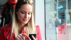 Νέο όμορφο ξανθό οδηγώντας τραμ γυναικών, που δακτυλογραφεί σε κινητό, τηλέφωνο, κύτταρο φιλμ μικρού μήκους