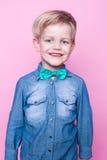 Νέο όμορφο παιδί που χαμογελά με τον μπλε δεσμό πουκάμισων και πεταλούδων Πορτρέτο στούντιο πέρα από το ρόδινο υπόβαθρο Στοκ φωτογραφία με δικαίωμα ελεύθερης χρήσης