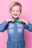 Νέο όμορφο παιδί που χαμογελά με τον μπλε δεσμό πουκάμισων και πεταλούδων Πορτρέτο στούντιο πέρα από το ρόδινο υπόβαθρο Στοκ Εικόνα