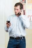 Νέο όμορφο περιστασιακό άτομο που χρησιμοποιεί δύο τηλέφωνα κυττάρων Στοκ Εικόνες