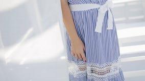 Νέο όμορφο πρότυπο στη ριγωτή χαλάρωση φορεμάτων κοκτέιλ στο πεζούλι της πολυτελούς τοποθέτησης θερέτρου ξενοδοχείων με τα χέρια  φιλμ μικρού μήκους