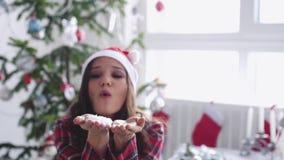 Νέο όμορφο φυσώντας κομφετί γυναικών από το δέντρο έλατο-Χριστουγέννων και το παράθυρο στο στούντιο κίνηση αργή 3840x2160 απόθεμα βίντεο
