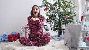 Νέο όμορφο φυσώντας κομφετί γυναικών brunette από το δέντρο έλατο-Χριστουγέννων και το παράθυρο στο στούντιο κίνηση αργή 3840x216 απόθεμα βίντεο