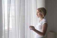 Νέο όμορφο χαμογελώντας κορίτσι που ανοίγει τις άσπρες κουρτίνες το πρωί Στοκ Εικόνα