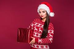 Νέο όμορφο χριστουγεννιάτικο δώρο εκμετάλλευσης γυναικών στα χέρια της στο κόκκινο υπόβαθρο στούντιο Στοκ φωτογραφίες με δικαίωμα ελεύθερης χρήσης