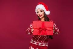 Νέο όμορφο χριστουγεννιάτικο δώρο εκμετάλλευσης γυναικών στα χέρια της στο κόκκινο υπόβαθρο στούντιο Στοκ Εικόνες