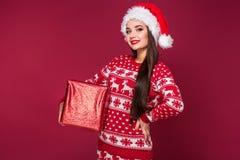 Νέο όμορφο χριστουγεννιάτικο δώρο εκμετάλλευσης γυναικών στα χέρια της στο κόκκινο υπόβαθρο στούντιο Στοκ Εικόνα