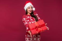 Νέο όμορφο χριστουγεννιάτικο δώρο εκμετάλλευσης γυναικών στα χέρια της στο κόκκινο υπόβαθρο στούντιο Στοκ φωτογραφία με δικαίωμα ελεύθερης χρήσης