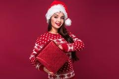 Νέο όμορφο χριστουγεννιάτικο δώρο εκμετάλλευσης γυναικών στα χέρια της στο κόκκινο υπόβαθρο στούντιο Στοκ εικόνα με δικαίωμα ελεύθερης χρήσης