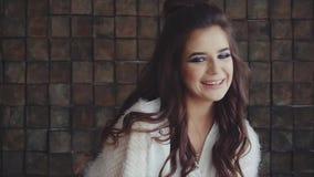 Νέο όμορφο brunette γυναικών που κοιτάζει στη κάμερα και το γέλιο φιλμ μικρού μήκους