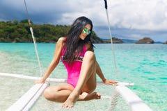Νέο όμορφο brunette που έχει τη διασκέδαση σε μια τροπική παραλία στο s Στοκ Φωτογραφίες