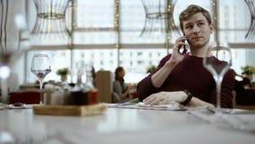 Νέο όμορφο freelancer που λειτουργεί στον πίνακα με το lap-top και που δακτυλογραφεί ένα μήνυμα στο τηλέφωνο Έννοια της εργασίας, απόθεμα βίντεο
