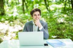 Νέο όμορφο freelancer που λειτουργεί στο lap-top στον πίνακα γραφείων στο πράσινο πάρκο χρυσή ιδιοκτησία βασικών πλήκτρων επιχειρ Στοκ φωτογραφία με δικαίωμα ελεύθερης χρήσης