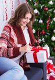 Νέο δώρο Χριστουγέννων ανοίγματος γυναικών κοντά στο χριστουγεννιάτικο δέντρο Στοκ φωτογραφία με δικαίωμα ελεύθερης χρήσης