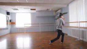 Νέο athlethic άτομο στην γκρίζα τζαζ χορού πουλόβερ σύγχρονη στη μεγάλη ελαφριά αίθουσα χορού με την μπάρα γύρω Χορεύοντας άτομο  φιλμ μικρού μήκους