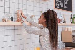 Νέο barista αφροαμερικάνων που παίρνει ένα βάζο γυαλιού με τα μπισκότα μακριά Στοκ Εικόνα