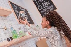 Νέο barista αφροαμερικάνων που παίρνει το βάζο γυαλιού με τα φασόλια καφέ μακριά Στοκ εικόνα με δικαίωμα ελεύθερης χρήσης