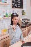Νέο barista αφροαμερικάνων που στέκεται πίσω από το μετρητή στη καφετερία με μια πετσέτα Στοκ Φωτογραφίες