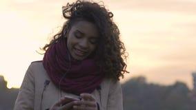 Νέο biracial χαμόγελο κοριτσιών, που ακούει την αγαπημένη μουσική της στη σύγχρονη συσκευή φιλμ μικρού μήκους