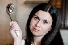 Νέο brunette με ένα εξυπηρετώντας κουτάλι στην κουζίνα Στοκ εικόνες με δικαίωμα ελεύθερης χρήσης