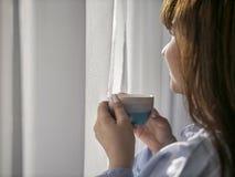 Νέο brunette με ένα φλιτζάνι του καφέ από το παράθυρο, κινηματογράφηση σε πρώτο πλάνο στοκ φωτογραφίες