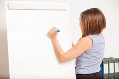 Νέο brunette που γράφει σε έναν πίνακα κτυπήματος Στοκ Φωτογραφία