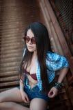 Νέο brunette στα γυαλιά ηλίου που κάθονται σε μια σκουριασμένη σκάλα Στοκ Φωτογραφίες