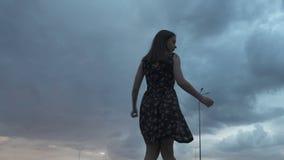 Νέο brunette στο θερινό φόρεμα που γυρίζει γύρω κάτω από το σκοτεινό ουρανό σύννεφων, εξάρτηση φιλμ μικρού μήκους