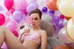 Νέο brunette Flirty που θέτει τις ιδιαίτερες προσοχές lollipop Στοκ Εικόνες