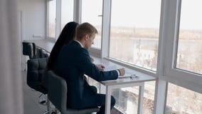 Νέο businesspeople που λειτουργεί στη συνεδρίαση επιχειρησιακού προγράμματος από το παράθυρο στο σύγχρονο γραφείο φιλμ μικρού μήκους