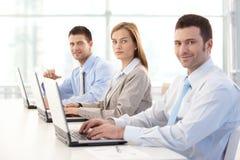 Νέο businesspeople που λειτουργεί στο χαμόγελο lap-top Στοκ Εικόνα