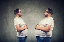 Νέο chubby άτομο που εξετάζει το λίπος ο ίδιος που αισθάνεται φουσκωμένο στοκ φωτογραφίες