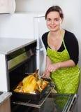 Νέο cockerel ψησίματος γυναικών χαμόγελου για το γεύμα στοκ εικόνες