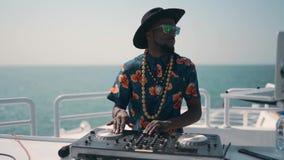 Νέο DJ που αναμιγνύει και που περιστρέφει στο θερινό κόμμα στη βάρκα DJ στην εργασία για τη θερινή θάλασσα στο Ντουμπάι απόθεμα βίντεο
